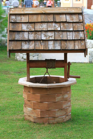 rural wooden bucket: Old wooden well and bucket of water inside on grass ground, primitive knowhow  Stock Photo