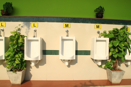 A row of urinals in decorate wall at public men toilet room  photo