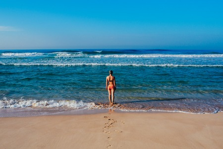 Beautiful surfer girl is enjoying vacation on the tropical beach. Young woman with surfboard in Sri Lanka.