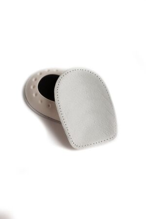 Orthopedic leather heel pad from corns for the correction of different lengths of legs isolated on white background. Leather insert for the forefoot. Medical insoles. Flat Feet Correction. Banco de Imagens