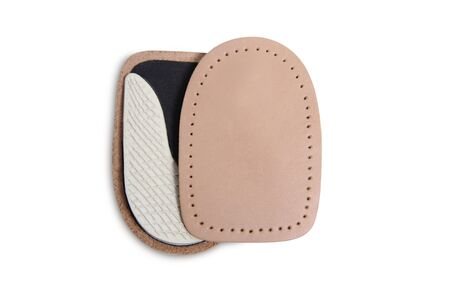 Orthopedic leather heel pad from corns for the correction of different lengths of legs isolated on white background. Leather insert for the forefoot. Medical insoles. Flat Feet Correction.