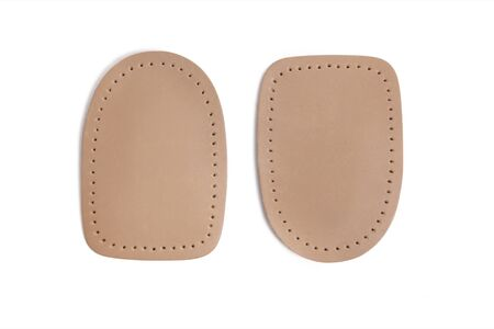 Orthopedic leather heel pad from corns for the correction of different lengths of legs isolated on white background. Leather insert for the forefoot. Medical insoles. Flat Feet Correction. Foto de archivo