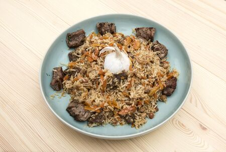 The concept of oriental cuisine. National Uzbek pilaf with meat on a ceramic dish, on a wooden table. background image. top view, copy space, flat lay Standard-Bild