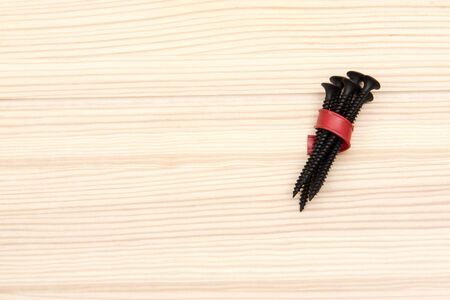 Black long screws tied with a red plastic strip. in the form of a bouquet, lie on a light wooden surface in the corner