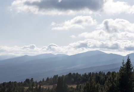 Panorama of the ridge of mountains. Light white clouds float above the mountains, the rays of the sun break through the light haze, the forest grows. Seven Rila Lakes, Bulgaria Stock fotó
