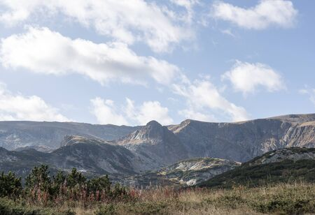Panorama of the mountain range. Light white clouds float over the mountains, sunny weather, morning. At the foot of the mountains, a forest grows. Seven Rila Lakes, Bulgaria