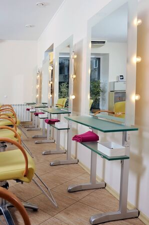 Khabarovsk, Russia, 10-05-2009. The interior of the hall of the beauty salon. Yellow chairs for clients, along the wall are illuminated mirrors and tables for working with clients.