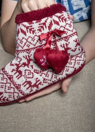 In the hands of the child is a large Christmas sock on which deer and hearts are drawn, and on the side two hearts with snowflakes drawn on them hang on a red ribbon