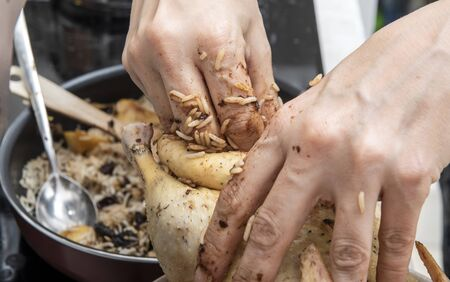 Close up of female hands stuffed with rice and prune duck filling. In the background is a filling pan and a wooden spatula.