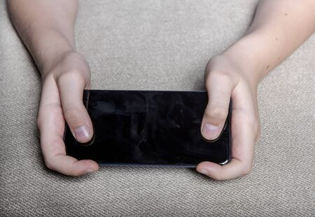 Child hands hold smartphone with black screen. Black screen smartphone. Background - gray coarse fabric.