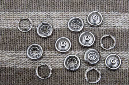 accessories for the production of jeans - a set of jeans buttons that lie on the textured mat