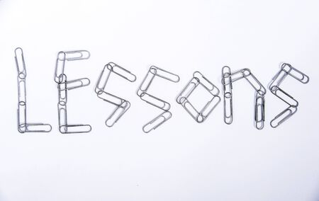 lessons - a word made up of small metal paper clips on a white background
