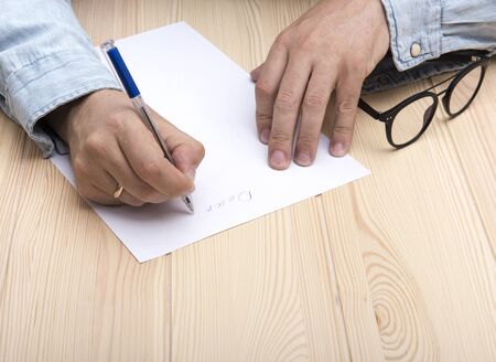 write a letter. In the hands of a man is a ballpoint pen and he writes a letter. Wedding ring on the hand. On a white sheet is the beginning of the letter. Nearby are glasses. Stock Photo