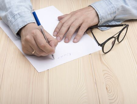 write a letter. In the hands of a man is a ballpoint pen and he writes a letter. Wedding ring on the hand. On a white sheet is the beginning of the letter. Nearby are glasses. 版權商用圖片