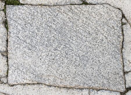 texture of the stone. Rectangular stone plates of gray granite color with mica elements. Sunny weather, day, the stone is evenly lit.