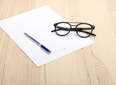 """write a letter. On a table made of light natural wood is a white sheet of paper. The inscription on the sheet is """"Dear."""" On a sheet of paper lies a ballpoint pen and glasses."""