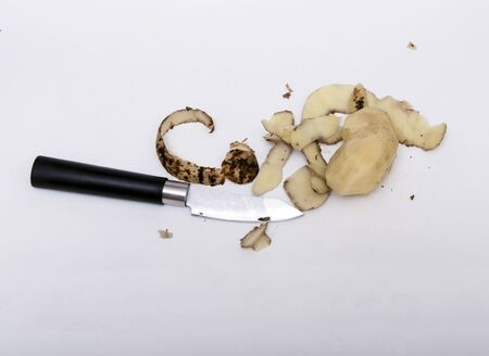 Peeling potatoes. On a white background lies a small knife with a black handle and peeled potatoes. Around the potato and knife lies the potato peel. Banco de Imagens
