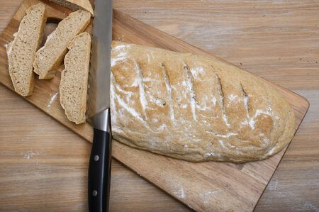 On a dark wooden cutting board lies a large bread knife and small pieces of chopped gray freshly made hand-made bread sprinkled with white flour, top view. Zdjęcie Seryjne