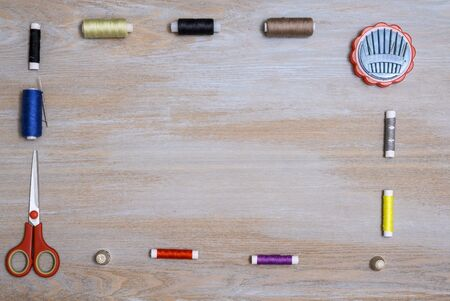 Spools of thread of different colors as well as scissors with red handles and a set of needles of different sizes with thimbles are laid out along the edge of a wooden vintage surface in the form of a frame