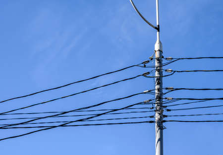 Electric pole and electric wires in black against the blue sky. An electrical pole to which there are groups of parallel lines of black electrical wires.