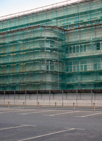 The building is covered with scaffolding and safety netting. Parking is located next to the building.