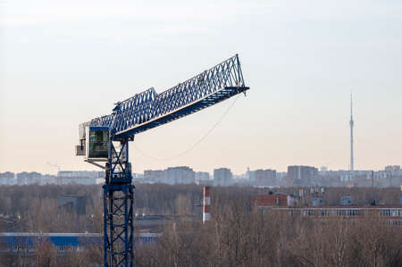 A construction tower crane froze in the sunlight against the backdrop of a city in the morning haze. The crane boom is installed towards the camera. Stock Photo