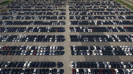 overproduction: Storage parking with new cars Stock Photo