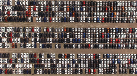 overproduction: Aerial view of huge storage parking with new cars