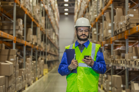Worker in uniform using mobile phone at warehouse