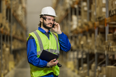 dispatcher: Worker speaking on mobile phone at warehouse Stock Photo