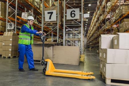 Lavoratore con la posa del camion di pallet