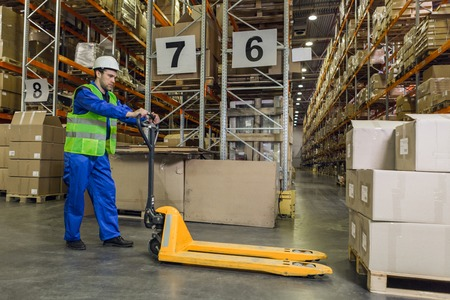 Worker with pallet truck posing