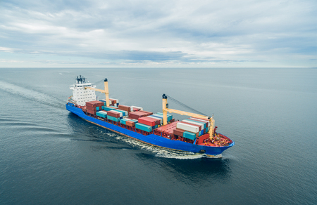 Aerial view of container vessel sailing in open sea