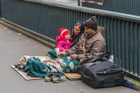 Homeless family sitting on the street Редакционное
