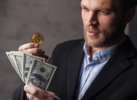 Uomo che tiene soldi e bitcoin Archivio Fotografico - 92769010