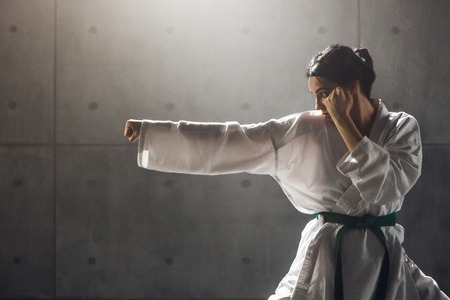 Woman in kimono practicing karate Banque d'images