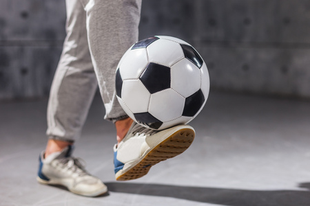 Man holds a soccer ball on his leg Stock Photo