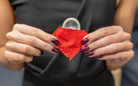 Woman holds a condom in her hands