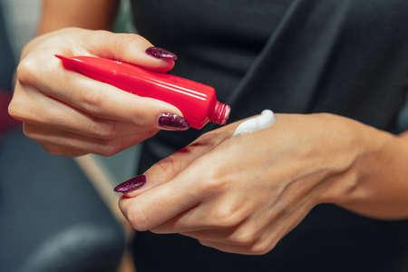 Woman applies hand cream 스톡 콘텐츠 - 159995098