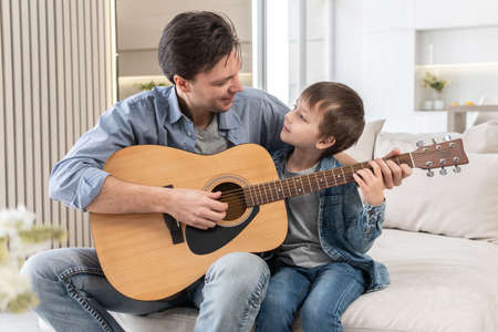 Father teaches son to play the guitar 스톡 콘텐츠