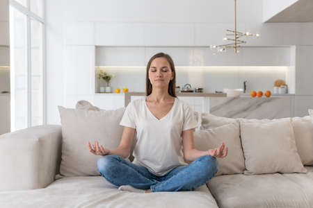 Young woman is sitting on a sofa and meditating 스톡 콘텐츠 - 164297608