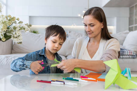 Mother and son cutting colored paper with scissors