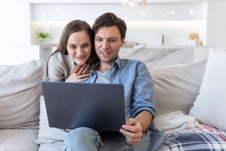 Cheerful couple looking at screen of laptop