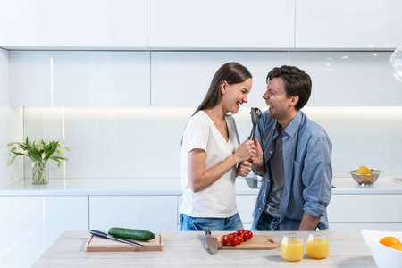 Cheerful couple having fun in the kitchen 스톡 콘텐츠 - 164544881