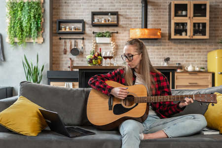 Woman is learning to play the guitar