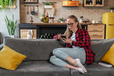 Young woman uses smartphone on sofa