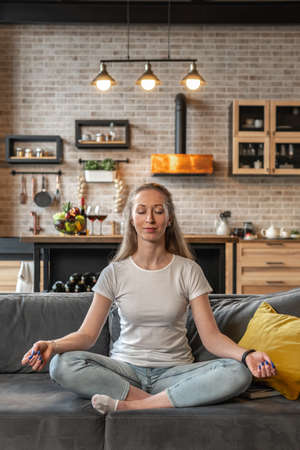 Young woman meditating on sofa 스톡 콘텐츠