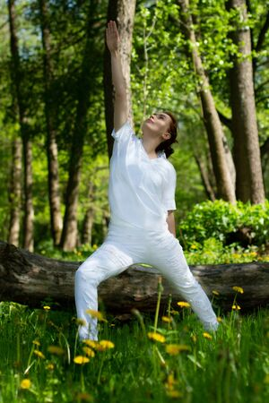 Beautiful girl practices yoga in peaceful nature atmosphere Stok Fotoğraf