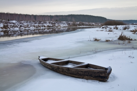 winter thaw: Wooden boat on the river during the winter thaw