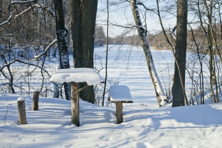 A wooden table by the lake in winter